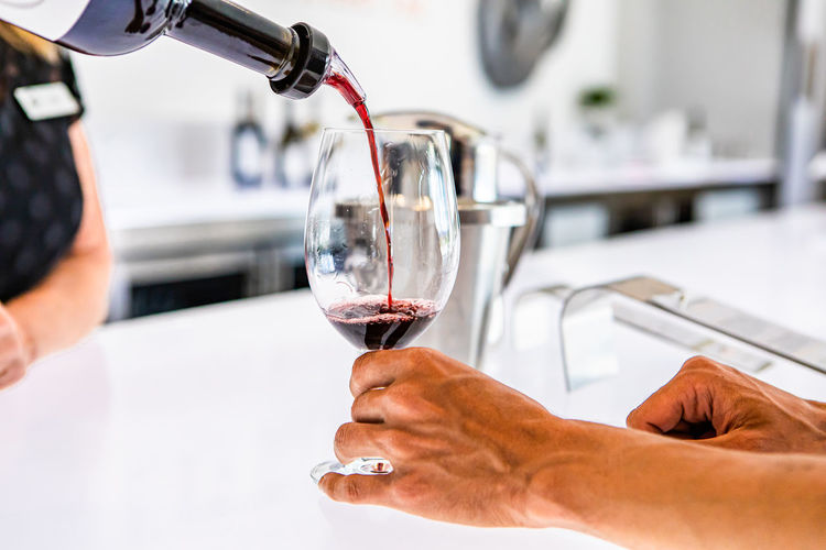 Close-up of hand pouring wine in glass