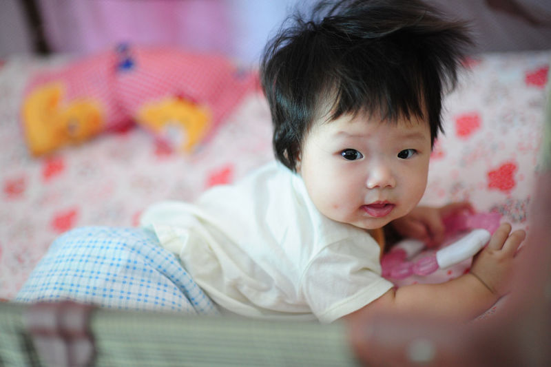 Portrait of cute baby girl in crib