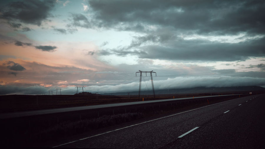 road iceland summer 24.00pm Cloud - Sky Sky Road Transportation Direction Sign The Way Forward Symbol Marking Connection Road Marking Nature No People Highway Overcast Dusk Beauty In Nature Empty Road Environment Outdoors Diminishing Perspective Electricity  Iceland