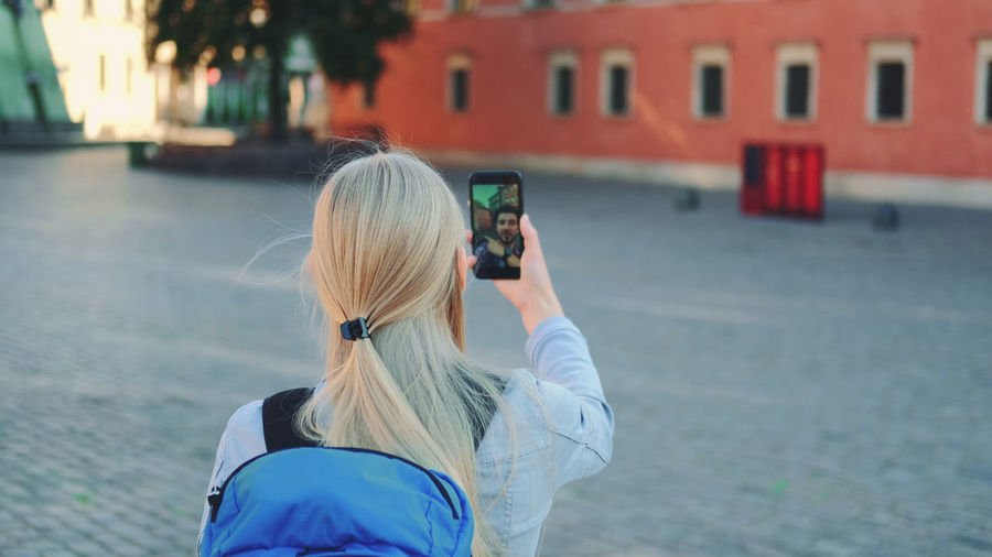Rear view of woman photographing with mobile phone in city