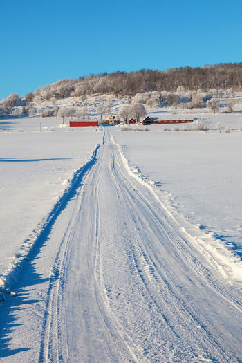 Snow covered road by land against blue sky