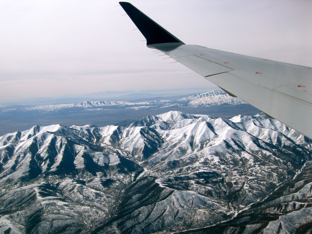 airplane, mountain, nature, airplane wing, scenics, beauty in nature, snow, cold temperature, aerial view, transportation, journey, no people, travel, sky, mountain range, landscape, winter, tranquil scene, air vehicle, outdoors, day, snowcapped mountain, flying, vehicle part