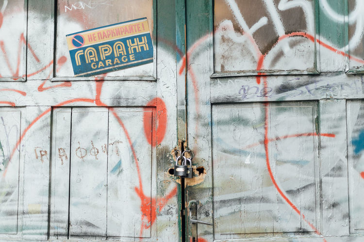Closed garage door with lock and grafitti Text Western Script Communication Day Architecture No People Sign Door Entrance Graffiti Outdoors Wall - Building Feature Close-up Building Exterior Closed Information Capital Letter Built Structure Guidance Safety Closed Door Prohibited Forbidden Lock