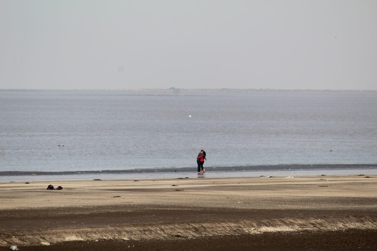 Couple On Beach Against Sky