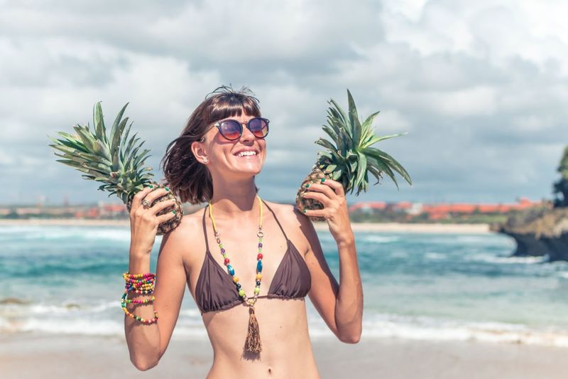 The girl laughs and holds pineapples in her hands. Model Pineapple Ocean View Summer Vacation Travel Traveling Travel Destinations Bali Bali, Indonesia Beach Water Land Sky Sunglasses Nature Sea Fashion Glasses Young Adult Day Swimwear Cloud - Sky Bikini Young Women One Person Front View Beautiful Woman Holiday Outdoors