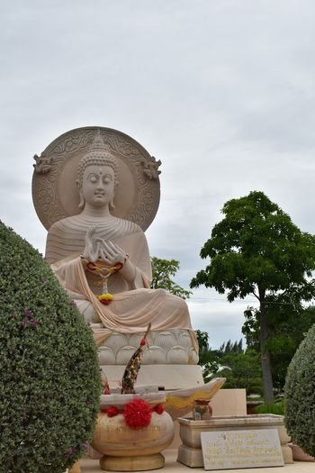 Low angle view of buddha statue against sky at temple
