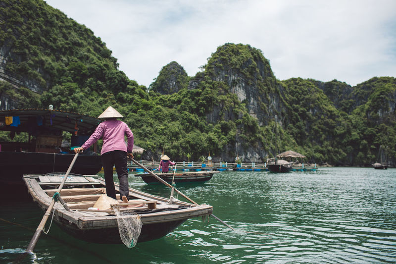 Rear View Of Woman Standing In Rowboat On Halong Bay By Mountains