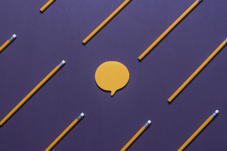 Communication concept with a post-it note, in shape of a speech bubble, surrounded by aligned orange pencils with erasers, on a purple background. Copy Space Office Blank Communication Crayon Education Memo Note Paper Note Post It Post It Notes Speech Bubble Still Life Studio Shot Wooden Pencil