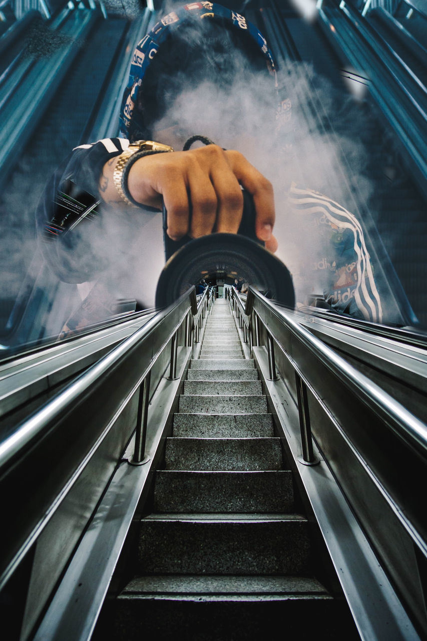 REAR VIEW OF MAN ON ESCALATOR IN SUBWAY
