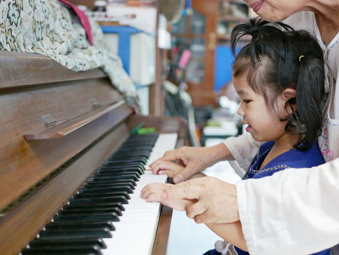 Midsection Of Grandmother Assisting Granddaughter In Playing Piano At Home