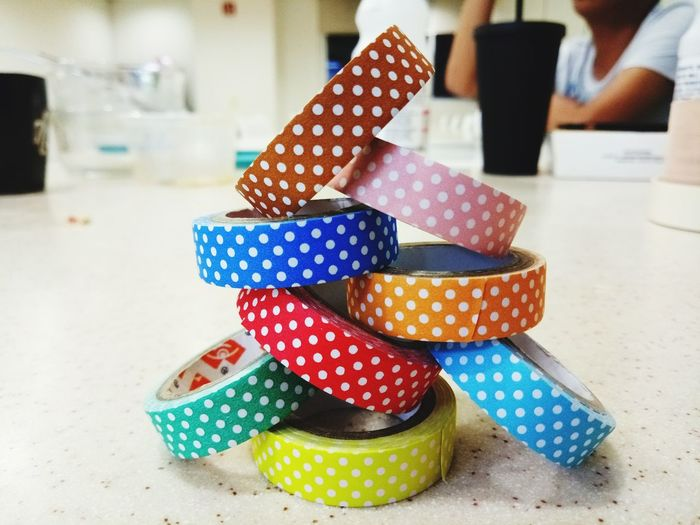 Close-up of stacked colorful adhesive tapes on table
