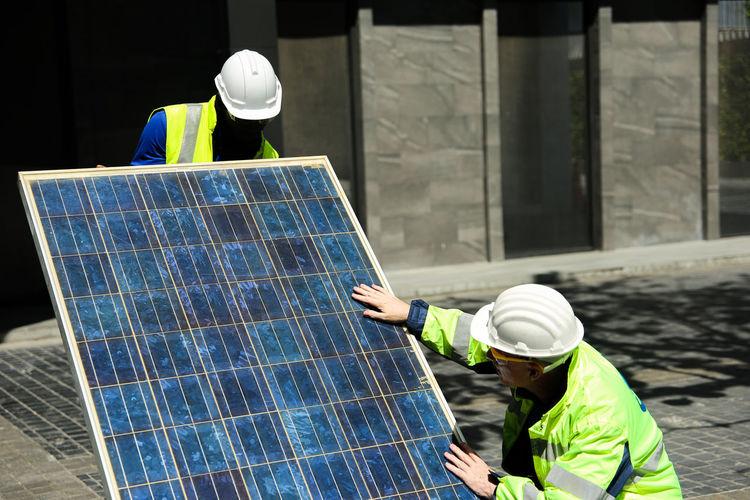 Engineers installing solar panel outdoors