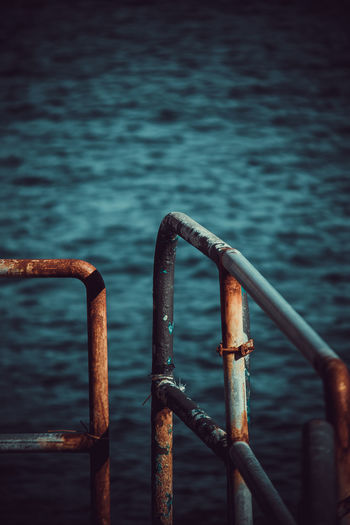 Close-up of rusty metal railing against sea