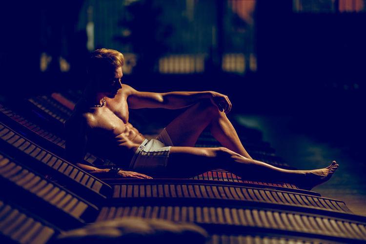 Shirtless muscular man relaxing on lounge chair at night