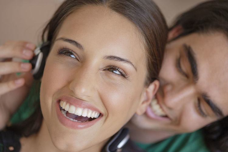 Young couple listening to music having fun 20-25 Years Old Fun Headphones Adult Beautiful Woman Close-up Emotion Happiness Headshot Human Face Indoors  Leisure Activity Lifestyles Make-up Portrait Positive Emotion Real People Smiling Teeth Togetherness Toothy Smile Two People Women Young Adult Young Women