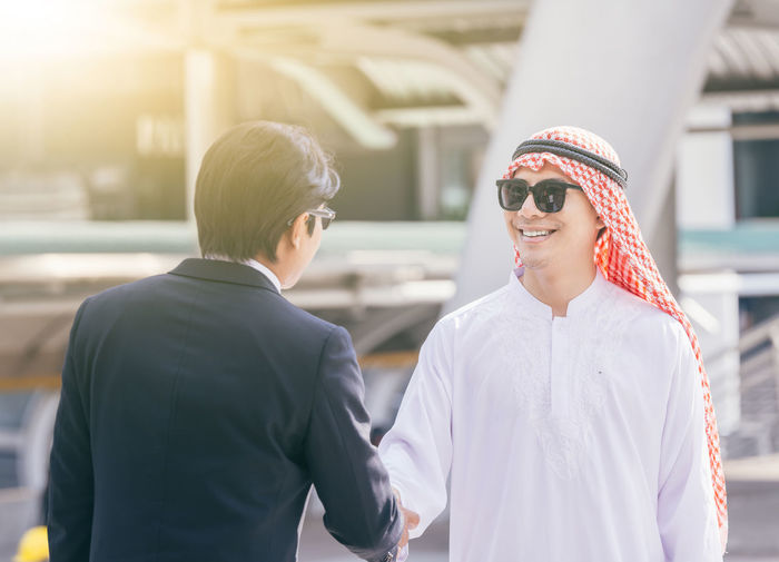 handshake concept.Arabic business and Businessman shaking hands Arabian Discussion Dubai Greeting Meeting Saudi Arabia UAE Agreement Arab Arabic Beard Businessman Communication Deal Handshake Handsome Partnership Partnership - Teamwork Portriat Scarf Smile Success Successful Sun Glasses Talking