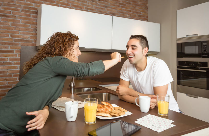 Happy young girl feeding her boyfriend with a cookie in weekend home breakfast Family Fruit Girlfriend Thirties Relaxing Husband Boyfriend 30s Wife Relationship Adult Lifestyle Interior Love Cup Caucasian Healthy Two Coffee Orange Girl Juice Meal Drink Together Young Woman Kitchen Man Indoors  Food Morning Technology Newspaper Digital Tablet Eating Feeding  Smiling Cheerful Happiness Smile Happy Male Home People Female Couple Breakfast