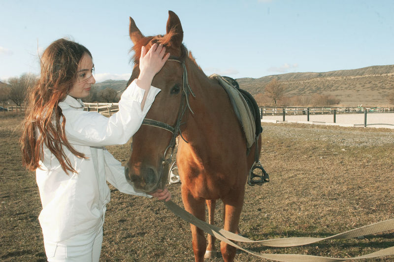 Young woman stroking horse while standing in animal pen