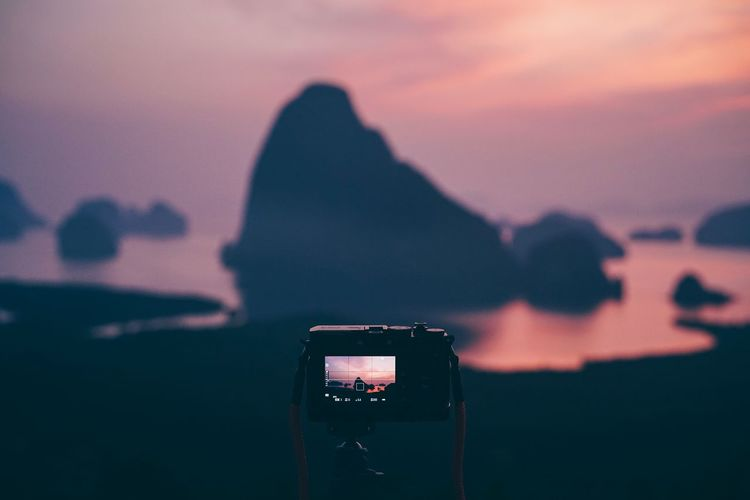 Close-up of camera photographing rock formation in sea against sky during sunset