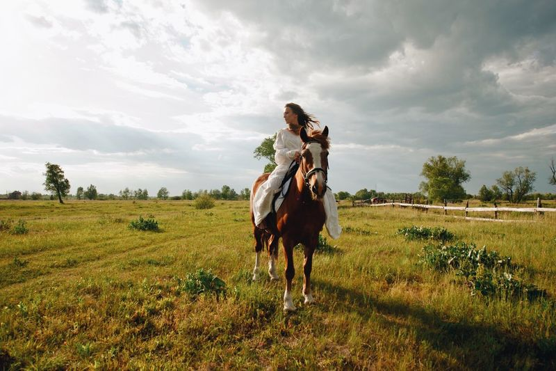 Young woman riding horse on field