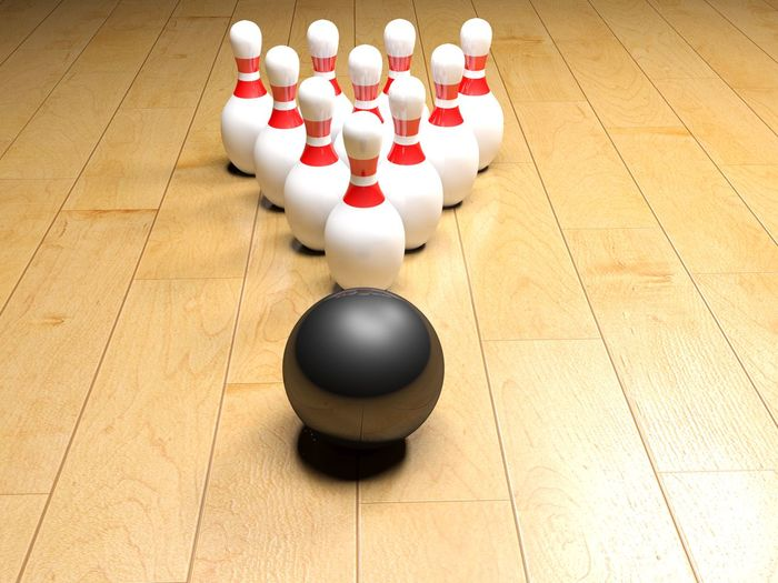 High angle view of bowling balls and pins on wooden floor