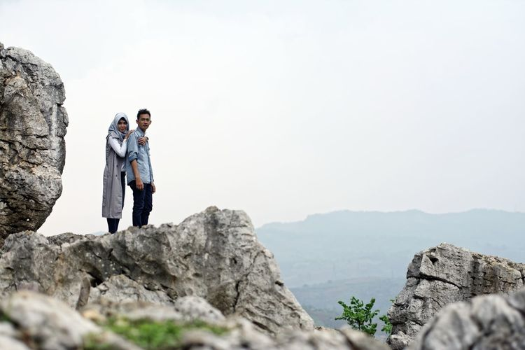 Couple standing on cliff against sky