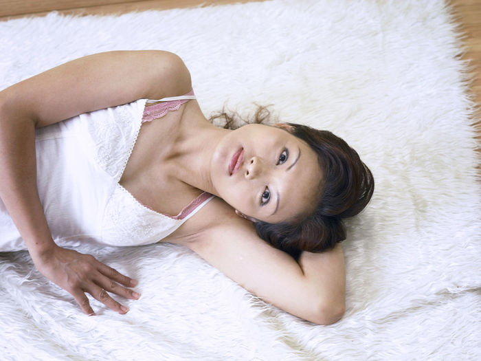 Mature Woman Lying On Fur Rug At Home