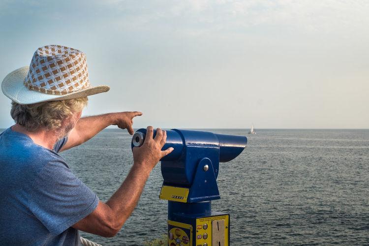 Man wearing hat against sea against sky