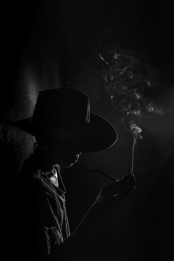 Obscured face of mature man holding cigarette while standing against black background