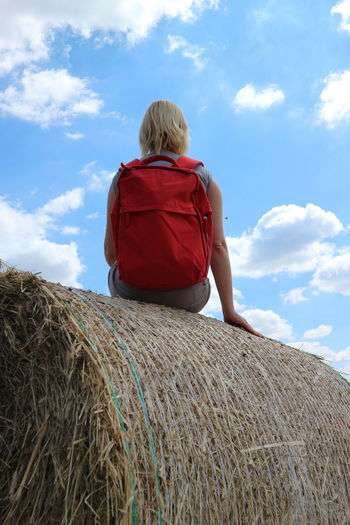Rear view of backpack woman sitting on hay bale
