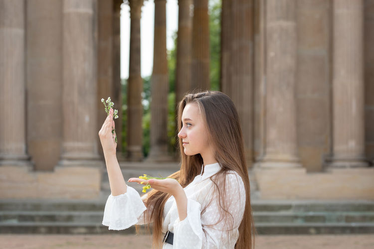 Close-up of young woman holding flower standing against columns
