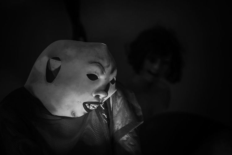 Close-up of person in costume and mask at darkroom