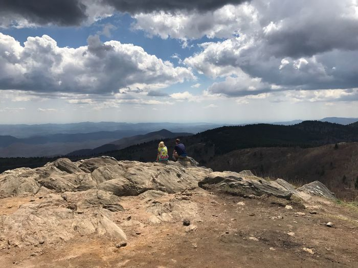 Hikers Sitting On Rock Against Cloudy Sky