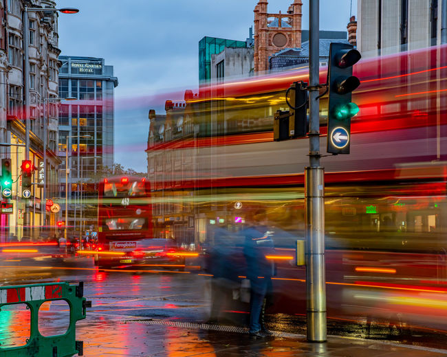 Blurred motion of vehicles on road by buildings in city