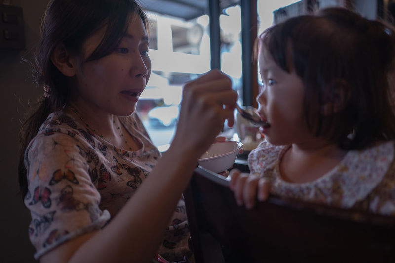 Woman feeding toddler daughter sitting on chair in restaurant