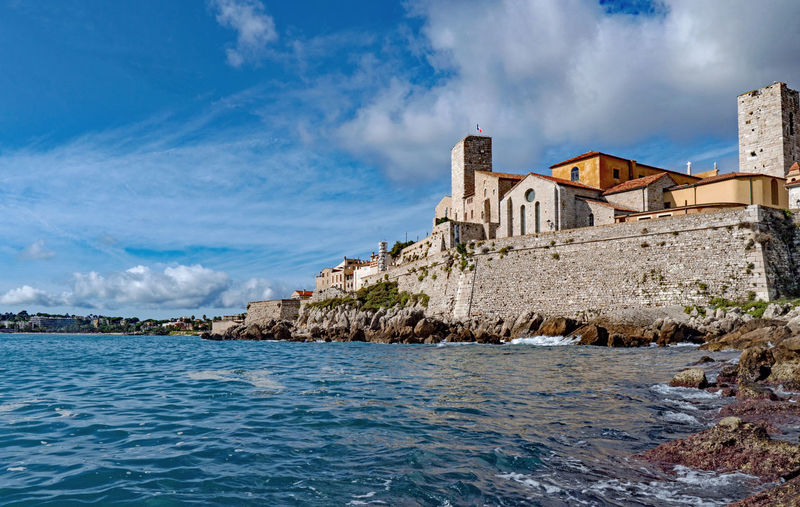 Buildings by sea against sky