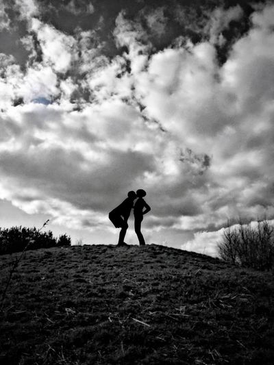 Silhouette man kissing woman on hill against cloudy sky