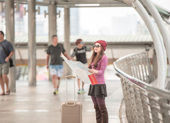 Woman With Luggage Reading Map While Standing On Footbridge In City
