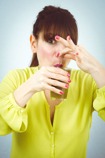 Funny Green Nail Polish Overcome Smoke Vegetarian Bad Brown Cover Disgusting  Drink Drinking Glass Front View Icky Nasty Nose One Person Sceptical Smell Taste Vegan Vegetarian Lifestyle  Yellow