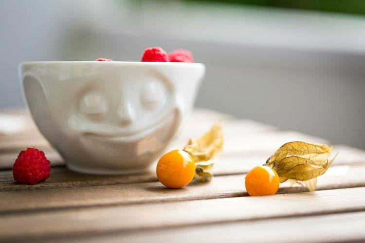 Raspberries in bowl by winter cherries on table