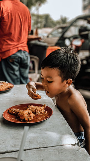 Side view of shirtless boy eating food while sitting on table