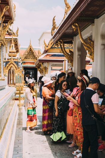 People standing outside temple against building