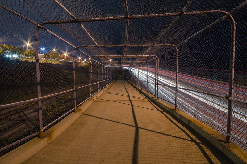 Covered walkway by light trails at night