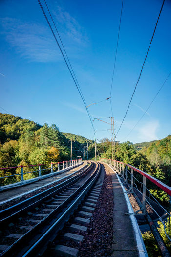 Blue Cable Connection Day Diminishing Perspective Direction Electricity  Mode Of Transportation Nature No People Outdoors Plant Power Line  Power Supply Public Transportation Rail Transportation Railroad Track Sky The Way Forward Track Transportation Tree
