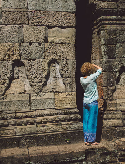 Siem Reap Cambodia Angkor Curly Hair Girl Architecture Built Structure Art And Craft Wall - Building Feature Real People One Person Creativity History Full Length The Past Lifestyles Building Exterior Representation Rear View Carving - Craft Product Leisure Activity Casual Clothing Ancient Day Stone Wall
