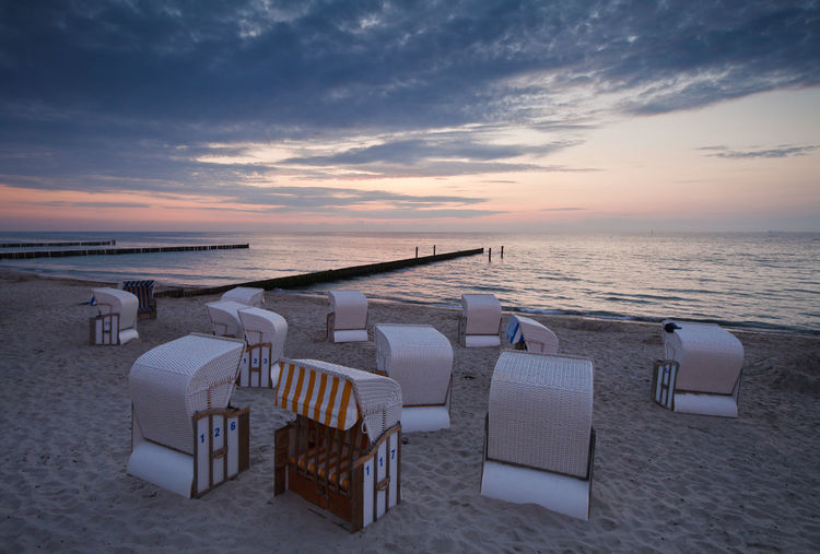 Sunset on shore of the Baltic Sea. Baltic Sea Beach Blue Calm Chair Empty Group Of Objects Hooded Beach Chair Horizon Over Water In A Row Lounge Chair Nature Nienhagen Germany Ocean Relaxation Sand Sea Seat Shore Sky Sunset Tranquil Scene Tranquility Vacations Water
