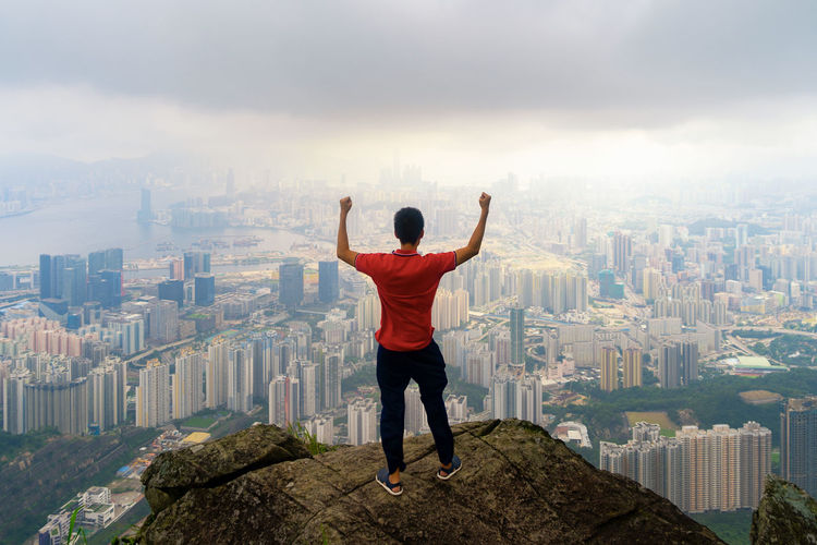 Rear view of man with arms raised standing against cityscape on rock