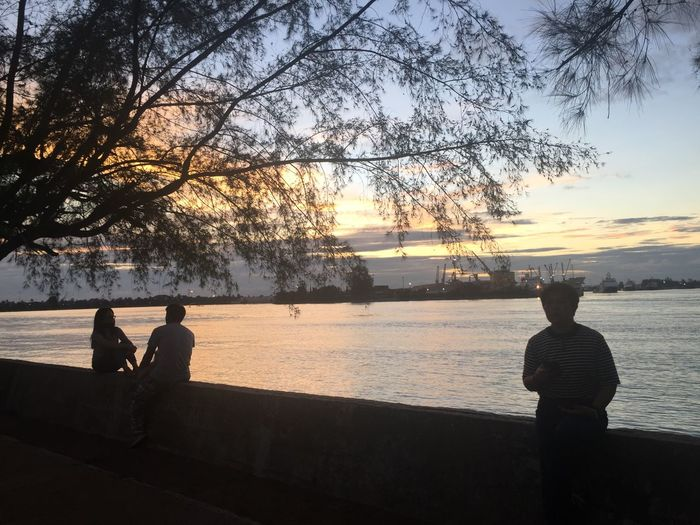 People sitting by lake against sky during sunset