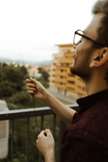 Portrait of young man holding eyeglasses against sky