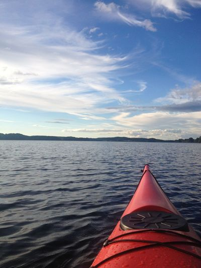 Kayak on sea against cloudy sky
